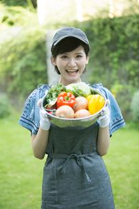 採れたての野菜を持つ笑顔の20代女性の写真素材 [FYI01740036]