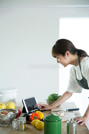 台に並べられた野菜と果物とタブレットを押す女性の指先の写真素材 [FYI01740038]