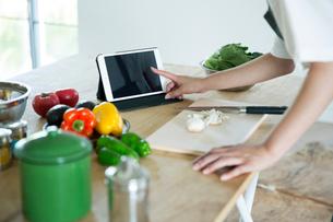 台に並べられた野菜と果物とタブレットを押す女性の指先の写真素材 [FYI01740070]
