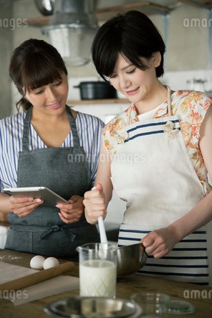 タブレットを確認しながらお菓子作りをする20代女性2人の写真素材 [FYI01740074]