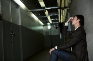 暗い廊下にしゃがみ考え込む男性の写真素材 [FYI01740123]