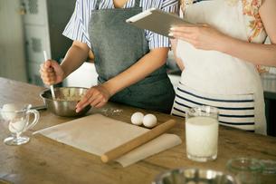 タブレットを確認しながらお菓子作りをする女性2人の手元の写真素材 [FYI01740124]
