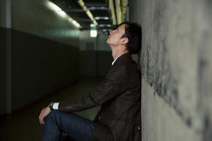 暗い廊下にしゃがみ考え込む男性の写真素材 [FYI01740164]