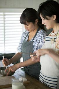 タブレットを確認しながらお菓子作りをする20代女性2人の写真素材 [FYI01740168]