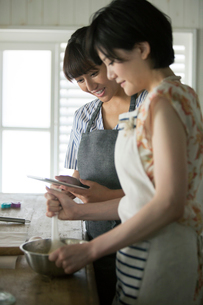 タブレットを確認しながらお菓子作りをする20代女性2人の写真素材 [FYI01740169]
