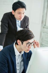 パソコンを確認する真剣な表情の20代男性2人の写真素材 [FYI01740232]