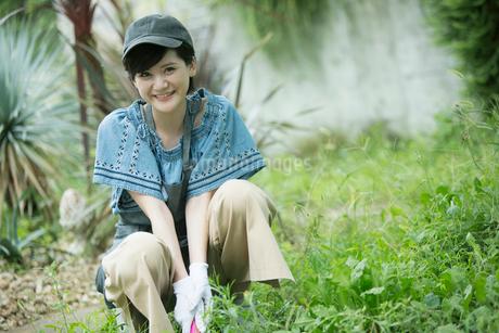 外で庭作業をする笑顔の20代女性の写真素材 [FYI01740240]
