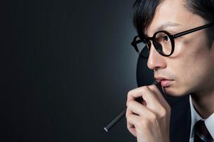 電子たばこを持つスーツ姿の男性の写真素材 [FYI01740251]