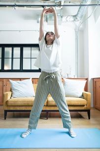 部屋でストレッチをする20代女性の写真素材 [FYI01740261]
