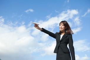 紙飛行機を飛ばすビジネスウーマンの写真素材 [FYI01743279]