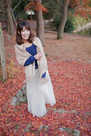 秋の紅葉の落ち葉の上の階段を歩く笑顔の女性の写真素材 [FYI01743877]
