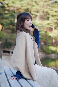 秋の紅葉の公園の池の前のベンチで電話をする女性の写真素材 [FYI01743887]