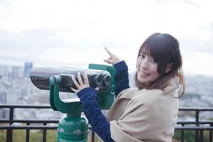 展望台から双眼鏡で神戸の景色を望む笑顔の女性の写真素材 [FYI01744011]
