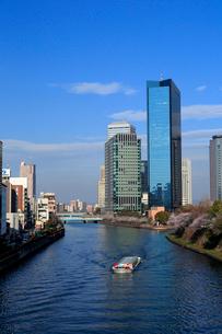 桜の季節のビジネスパークと観光船の写真素材 [FYI01744848]