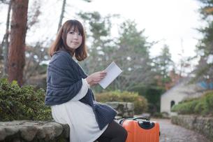 秋の石畳にトランクを置いて本を読む女性の写真素材 [FYI01744960]