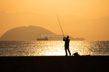 朝日金色に輝く海と釣り人の写真素材 [FYI01747584]