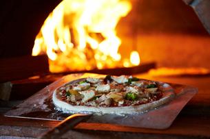 ピザ釜でピザを焼いているイメージの写真素材 [FYI01755416]