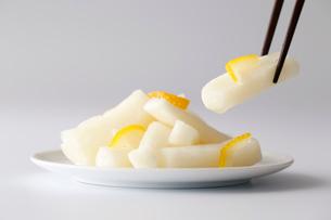 大根甘酢ゆず風味漬(白バック)を箸で持ち上げている写真の写真素材 [FYI01757802]