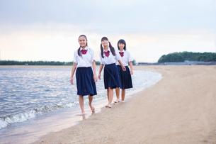波打ち際を歩く中学生の写真素材 [FYI01758911]