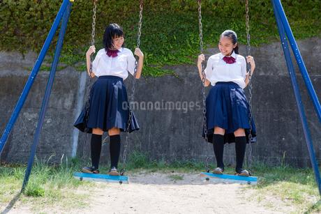 ブランコを立ち漕ぎする中学生の写真素材 [FYI01759173]