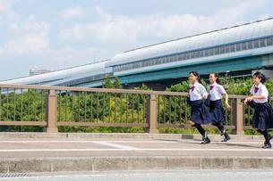 橋の上を走る中学生の写真素材 [FYI01759187]