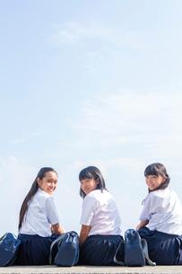 堤防で座りながら振り向く中学生の写真素材 [FYI01759237]