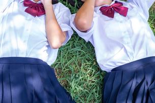 草の上に寝転がる中学生の写真素材 [FYI01759250]