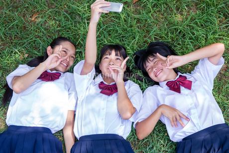 草の上に寝転がって写真を撮る中学生の写真素材 [FYI01759276]