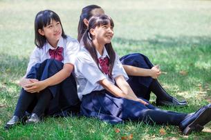 原っぱに背中合わせで座る中学生の写真素材 [FYI01759287]