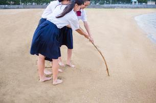 砂浜に文字を書く中学生の写真素材 [FYI01759320]