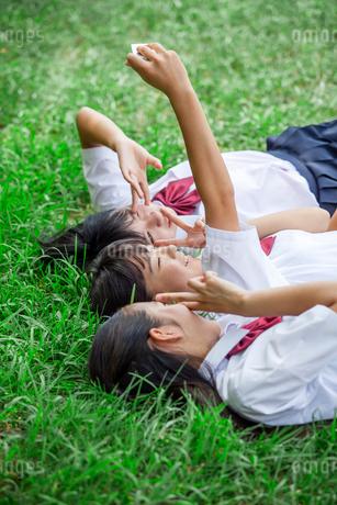 原っぱに寝転がる中学生の写真素材 [FYI01759354]