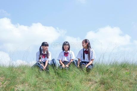 土手に座る中学生の写真素材 [FYI01759370]