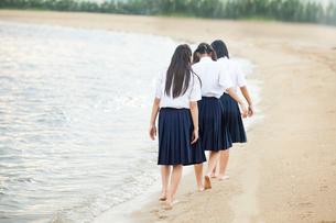 波打ち際を歩く中学生の写真素材 [FYI01759465]