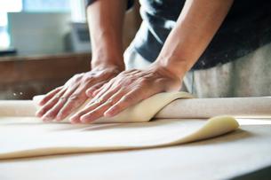 手打ちうどんの生地を麺棒でのばす工程写真の写真素材 [FYI01759469]