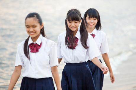 波打ち際を歩く中学生の写真素材 [FYI01759645]