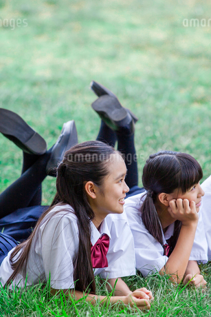 原っぱにうつぶせで頬杖をつく中学生の写真素材 [FYI01759681]