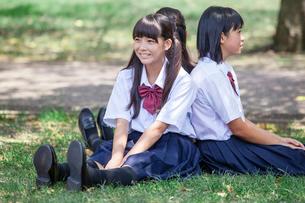 原っぱに背中合わせで座る中学生の写真素材 [FYI01759746]