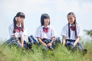 土手でおしゃべりする中学生の写真素材 [FYI01759979]