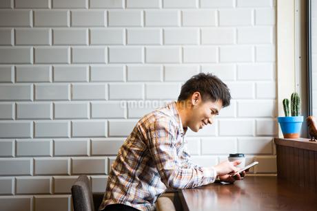 カフェでスマホを使う男性の写真素材 [FYI01760134]