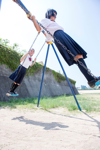 ブランコを立ち漕ぎする中学生の写真素材 [FYI01760375]