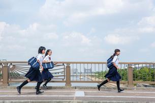 橋の上を走る中学生の写真素材 [FYI01760533]