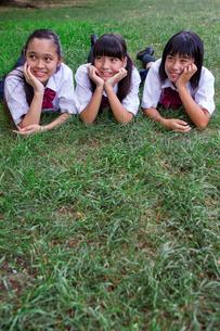 草の上にうつぶせで頬杖をつく中学生の写真素材 [FYI01760738]