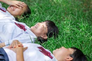 原っぱに寝転がる中学生の写真素材 [FYI01760965]
