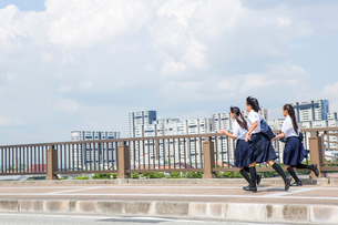 橋の上を走る中学生の写真素材 [FYI01760989]
