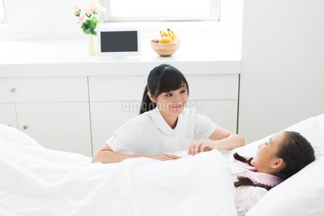 ベッドで寝る女の子と看護師の写真素材 [FYI01761069]