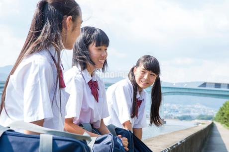 堤防で話す中学生の写真素材 [FYI01761093]