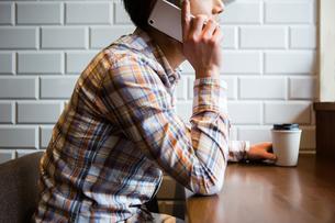 カフェでスマホを使う男性の写真素材 [FYI01761112]