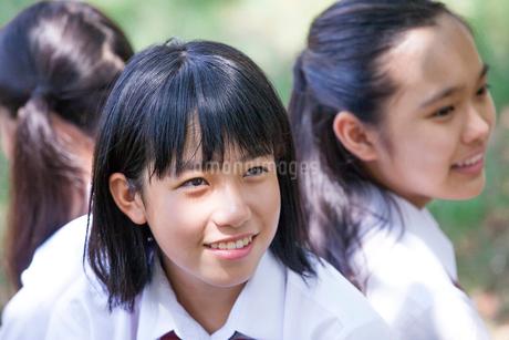 原っぱに背中合わせで座る中学生の写真素材 [FYI01761113]