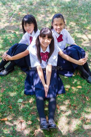 草の上に背中合わせで座る中学生の写真素材 [FYI01761160]