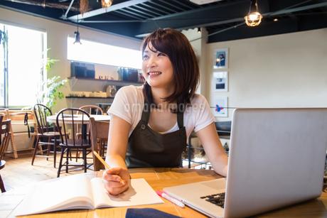 パソコンを使うカフェ店員の写真素材 [FYI01761173]